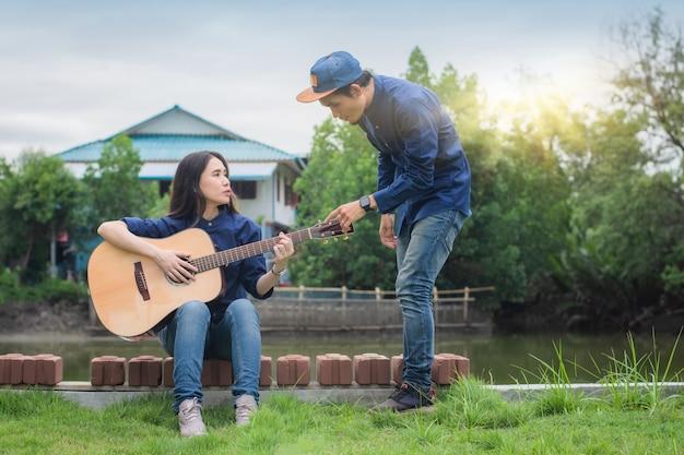 Due amici suonano la chitarra in estate felici in vacanza