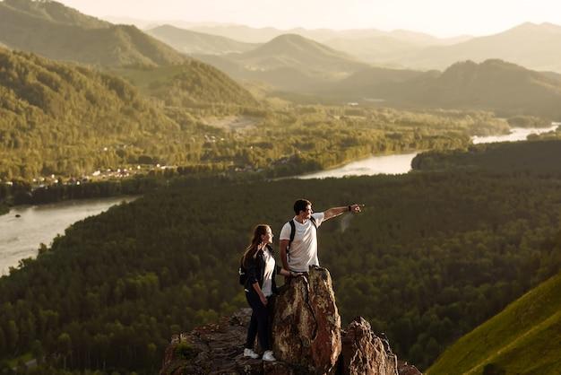 Due persone uomo e donna su una roccia in montagna che domina la valle e il fiume al tramonto