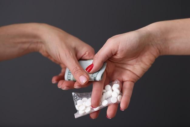 Due persone si scambiano pillole e denaro concetto di droghe proibite