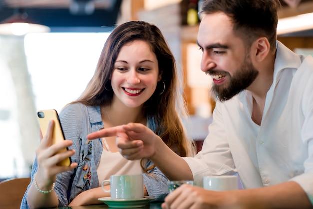 Due persone che usano un telefono cellulare insieme mentre bevono una tazza di caffè in una caffetteria.