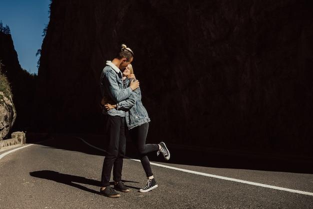 Due persone che camminano e abbracciano su una strada asfaltata vuota diritta ampia in montagna.