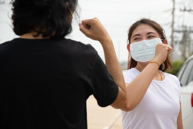 Due persone indossano la maschera facciale si stringono la mano
