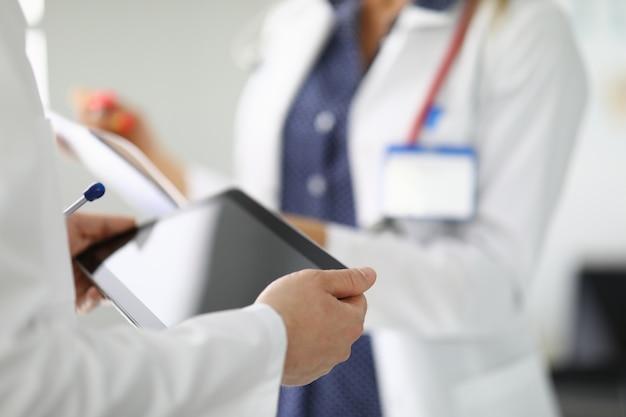 Due persone in camice bianco uno in possesso di un secondo tablet appunti