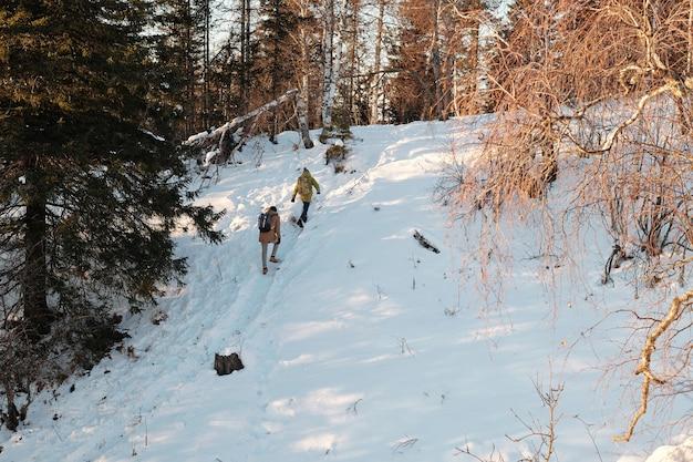 Due persone con zaini che salgono su una collina mentre si spostano lungo il sentiero