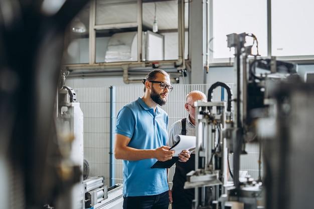 Due persone lavorano nello stabilimento su macchine speciali, focalizzate sul lavoro