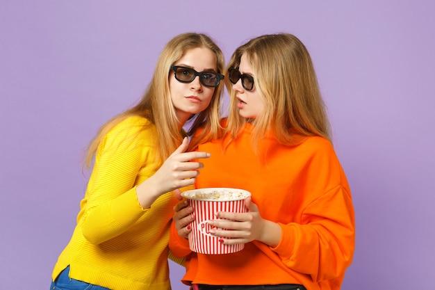 Due giovani sorelle gemelle bionde perplesse in occhiali 3d imax che guardano film, tengono il popcorn isolato sulla parete blu viola pastello. concetto di stile di vita familiare di persone.