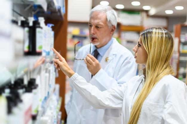 Due farmacisti, uomo e donna, alla ricerca di un prodotto su uno scaffale