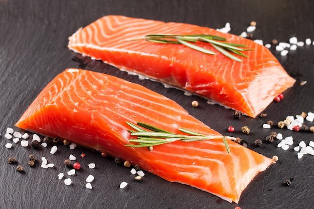 Due pezzi di filetto di salmone fresco con spezie su una superficie di ardesia nera