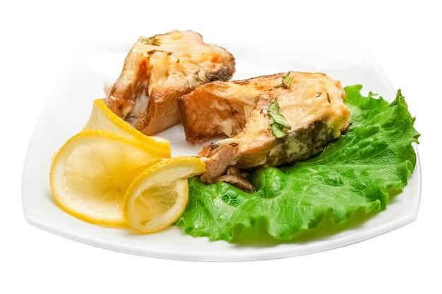 Due pezzi di pesce fritto con foglie di insalata verde e limone su sfondo bianco. oggetto isolato