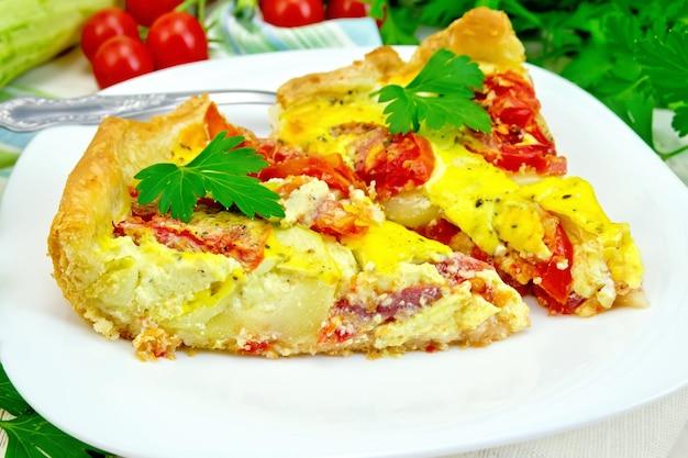 Torta di due pezzi di zucchine con pomodori e uova in un piatto bianco su un tovagliolo, prezzemolo su uno sfondo di assi di legno