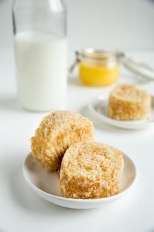 Due pezzi di pan di spagna con crema sul piatto bianco con una bottiglia di vetro di latte su bianco