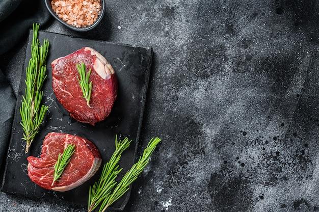 Due pezzi di bistecca sottile tagliati dal filetto. vista dall'alto. copia spazio.