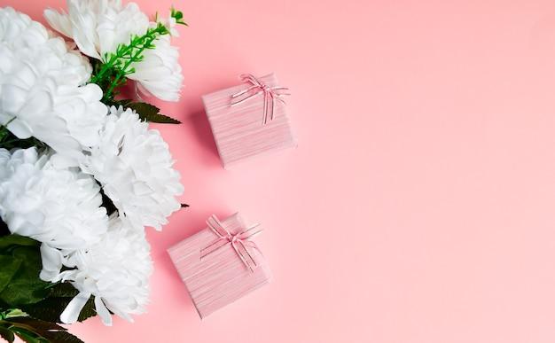 Confezione regalo due rosa con fiocco in nastro dorato. sfondo rosa floreale con spazio di copia.