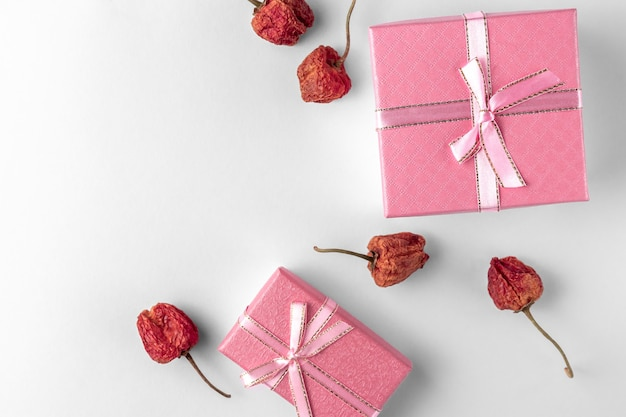 Due scatole regalo rosa con nastro, fiocco, fiori secchi isolati su uno sfondo bianco o grigio chiaro, ombra naturale, vista dall'alto