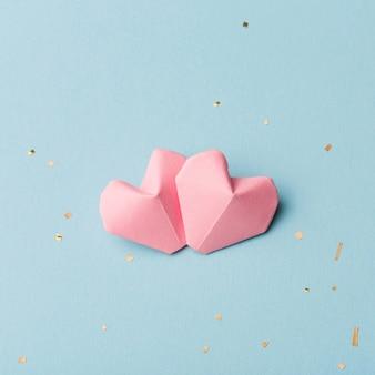 Due cuori rosa e orpelli dorati su sfondo azzurro Foto Premium