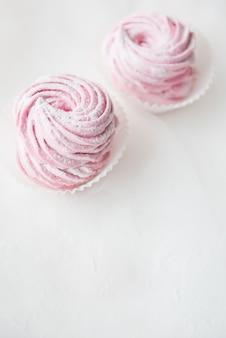 Arricciatura di marshmallow due rosa su sfondo bianco. copia spazio
