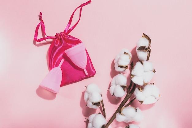 Due coppe mestruali rosa su una borsa di stoffa rosa e un ramo di cotone su uno sfondo rosa