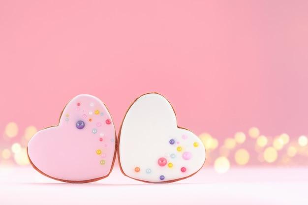 Due cuori rosa e bianchi a forma di pan di zenzero per san valentino, festa della mamma o compleanno su sfondo rosa.