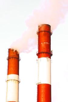 Due tubi e fumo. primo piano dal basso del fumo che esce dai tubi contro il cielo blu. due camini con denso fumo bianco. concetto di inquinamento atmosferico, problemi ambientali, emissioni atmosferiche. copia spazio