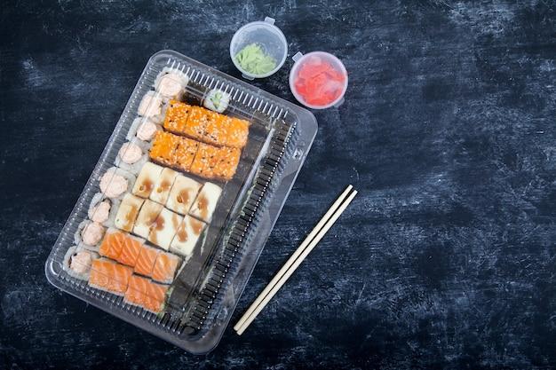 Due scatole di plastica con set di rotoli, wasabi e zenzero, bacchette di bambù su sfondo nero.