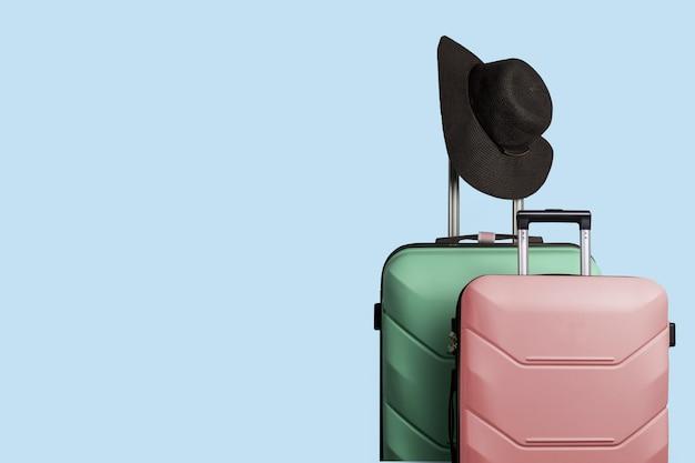 Due valigie di plastica su ruote e un cappello a tesa larga sul manico di una grande valigia su uno sfondo blu. concetto di viaggio, viaggio di vacanza, visita di parenti