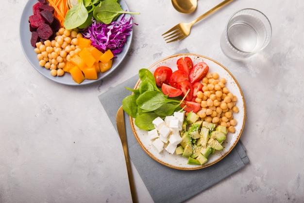 Due piatti buddha ciotole e bicchiere d'acqua. concetto per un pasto equilibrato disintossicante vegetariano sano. vista dall'alto. copia spazio.