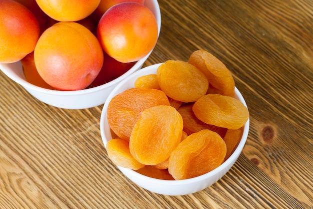 Due piatti con albicocche combinate fresche e secche, bel colore della frutta