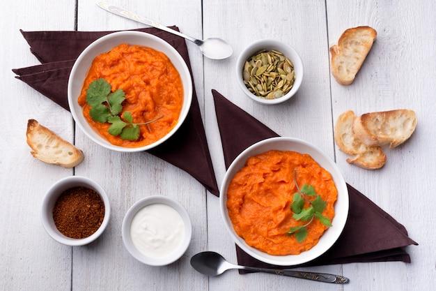 Due piatti con un contorno di zucca con crostini, panna acida, semi di zucca, coriandolo e spezie su un fondo di legno bianco.