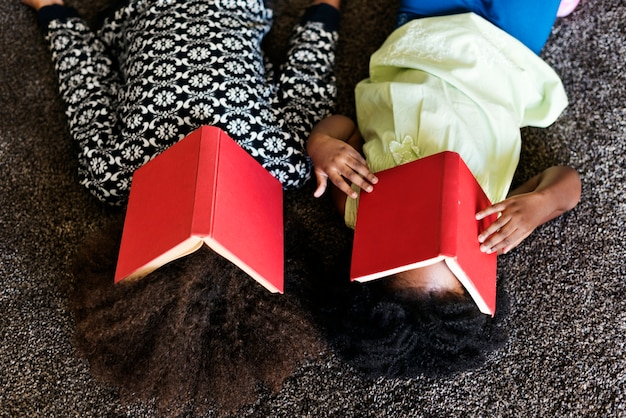 Due bambini africani giocosi con libri coperti sui loro volti