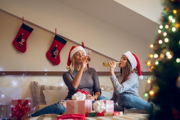 Due amiche giocose con il cappello di babbo natale seduto sul letto per le vacanze di natale e festeggiano bevendo birra