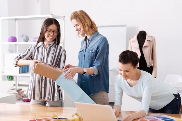 Due piacevoli donne ottimiste che imballano una scatola con un vestito in una borsa blu mentre il loro collega controlla una destinazione su un laptop