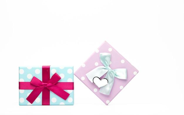Contenitore di regalo punteggiato a due polka con fiocco in nastro e biglietto di auguri in bianco isolato su sfondo bianco con spazio di copia, basta aggiungere il tuo testo. utilizzare per il festival di natale e capodanno