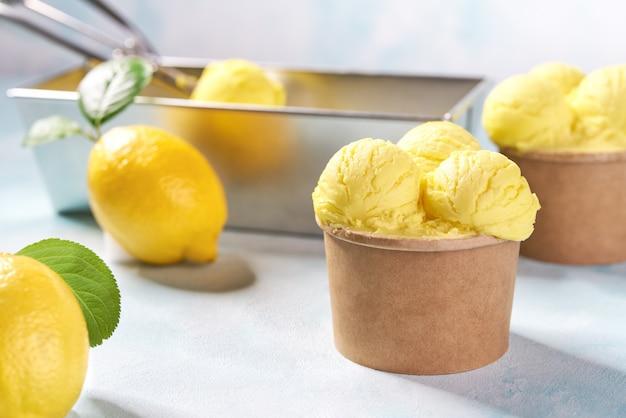 Il gelato al limone di due porzioni in tazza di carta sulla menta colora il fondo