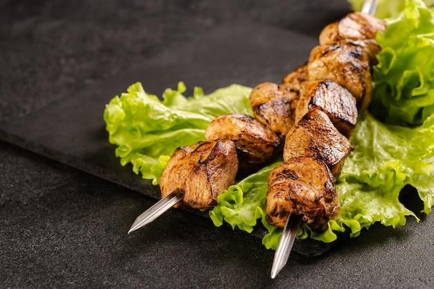 Due porzioni di shish kebab su una lastra di pietra con insalata.