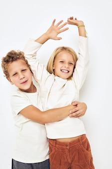 Due bambini in età prescolare, ragazzo e ragazza, abbracciano il fondo isolato di un'infanzia divertente