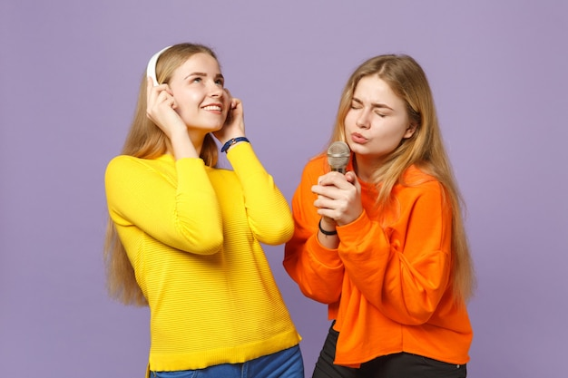 Due belle sorelle gemelle bionde in abiti colorati ascoltano musica con le cuffie, cantano una canzone nel microfono isolato sulla parete blu viola. concetto di stile di vita familiare di persone.