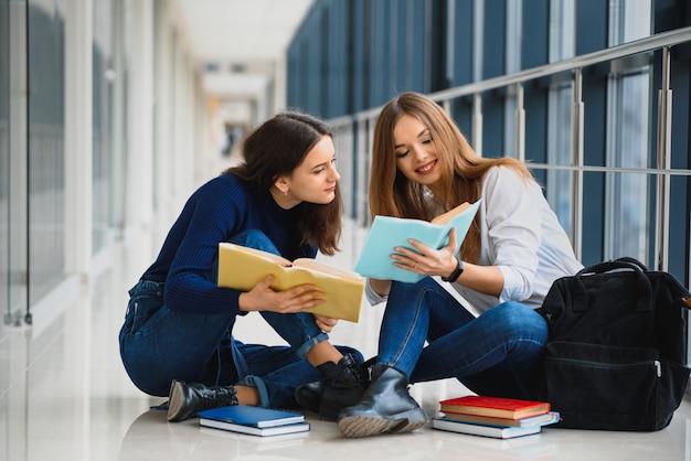 Due studentesse graziose con i libri che si siedono sul pavimento nel corridoio dell'università