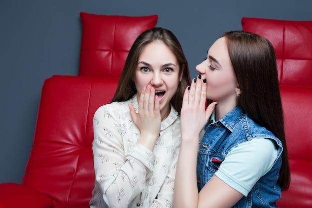 Due belle ragazze che spettegolano sullo strato di cuoio rosso
