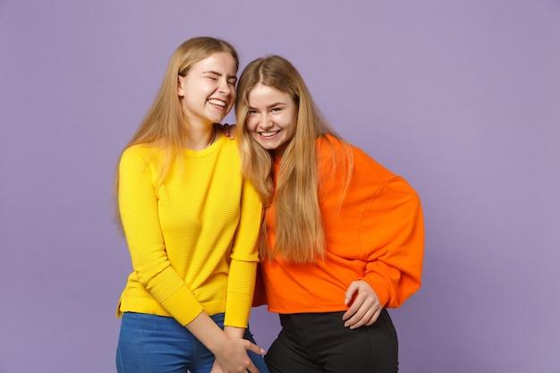 Due giovani sorelle gemelle bionde abbastanza felici in abiti colorati vividi in piedi isolate sulla parete blu viola pastello. concetto di stile di vita familiare di persone.