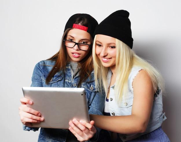Due ragazze graziose hipster che prendono un autoritratto con un tablet, sopra bianco, non isolato