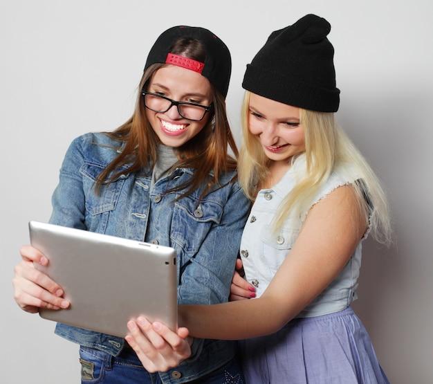 Due ragazze graziose dei pantaloni a vita bassa che prendono un autoritratto con un tablet