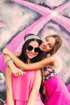 Due ragazze graziose dei pantaloni a vita bassa delle sorelle che abbracciano e che si divertono insieme