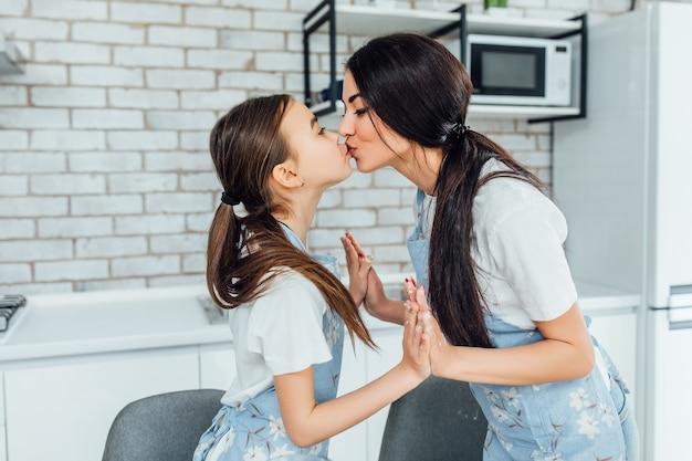 Due belle sorelle si baciano mentre fanno le torte in cucina