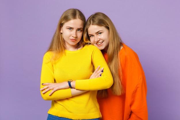 Due giovani sorelle gemelle bionde piuttosto sorridenti in abiti colorati vividi in piedi, isolate sulla parete blu viola pastello. concetto di stile di vita familiare di persone.