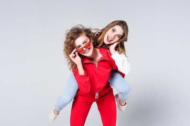 Due amici di ragazze abbastanza sorridenti che stanno isolati sopra gray, esaminando gli occhiali da sole. ragazze sorridenti. emozioni sorprese.