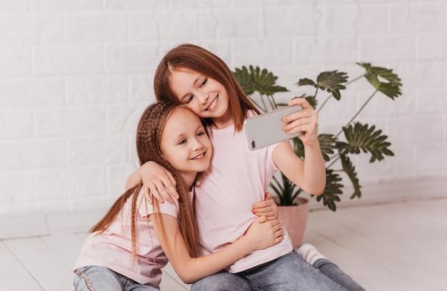 Due belle ragazze adolescenti guardano lo schermo dello smartphone e sorridono. selfie, video