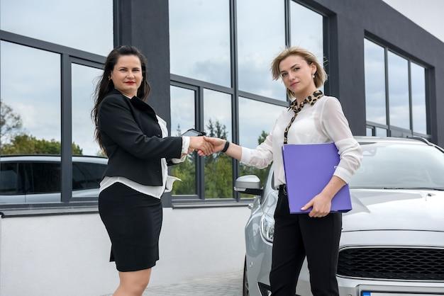 Due belle donne con cartelle in piedi vicino a un'auto nuova. esaminano alcuni documenti in cartelle