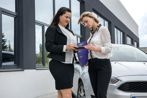 Due belle donne con le cartelle in piedi vicino alla macchina nuova