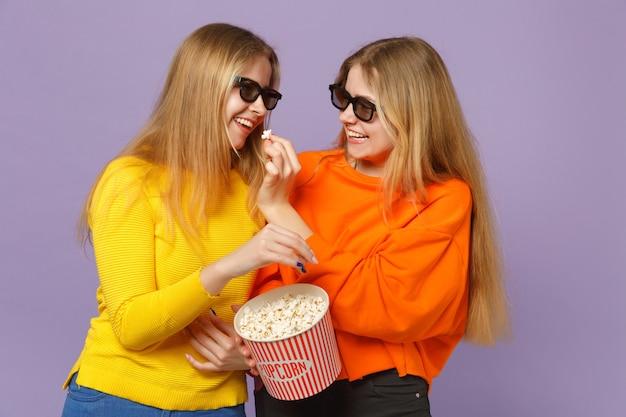 Due belle giovani sorelle gemelle bionde ragazze in occhiali 3d imax che guardano film, tenendo popcorn isolato su parete blu viola pastello concetto di stile di vita familiare di persone.