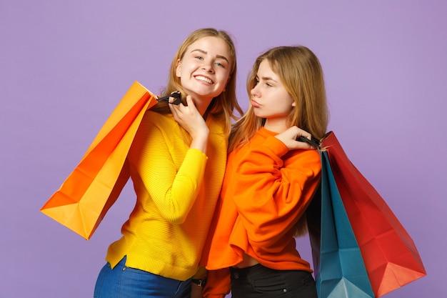 Due belle giovani sorelle gemelle bionde ragazze in abiti vivaci che tengono la borsa del pacchetto con gli acquisti dopo lo shopping isolato sulla parete blu viola. concetto di stile di vita familiare di persone.